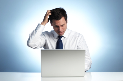 Man Scratching Head at Computer